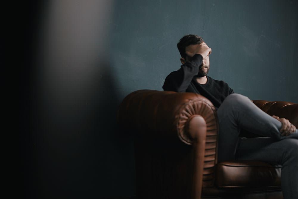 Homem sentado em poltrona com semblante muito preocupado e cobrindo os olhos com mão. Representa a Síndrome de burnout em Advogados