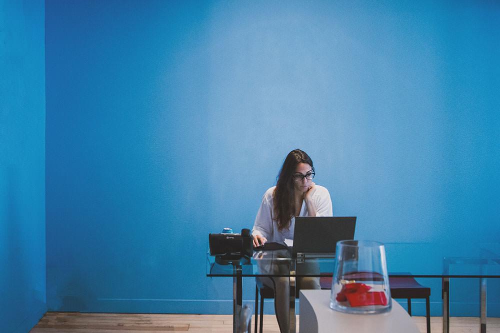Uma advogada trabalhando sozinha em uma sala através de um notebook sobre uma mesa de vidro. Imagem demonstra a possibilidade de