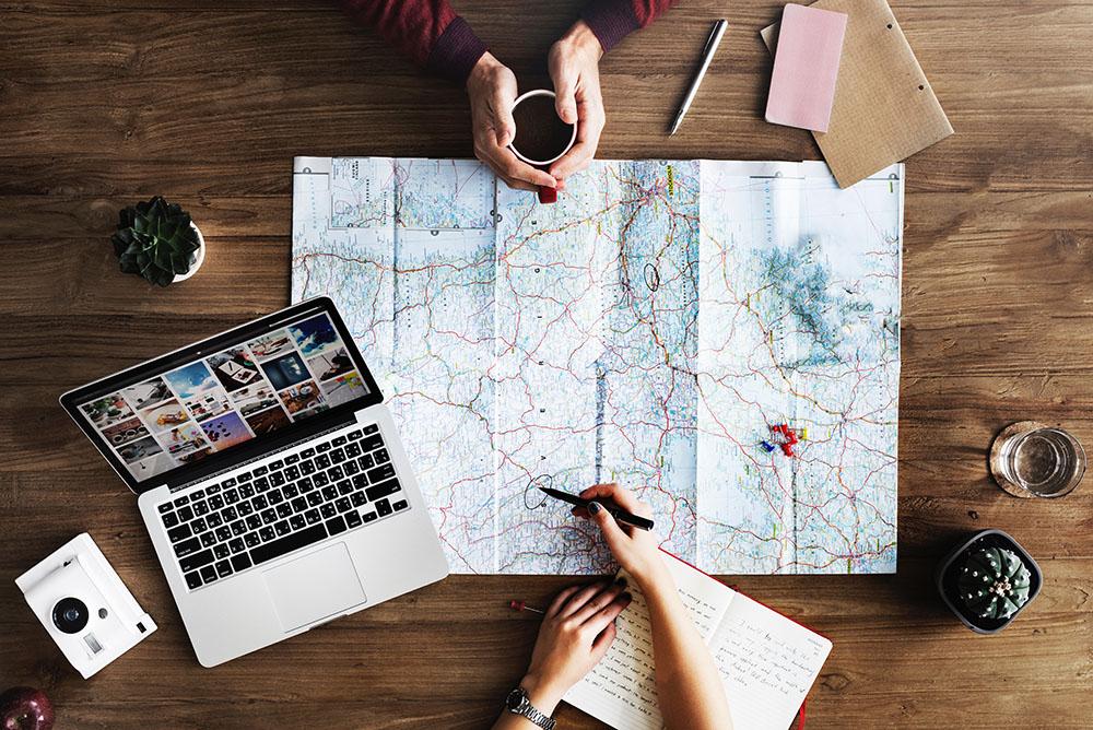 Uma foto aérea de uma mesa. Sobre ela, um notebook, blocos e caneta para anotação, e duas pessoas traçando rota em um mapa. representa a expansão geográfica permitida pelo Atendimento jurídico digital