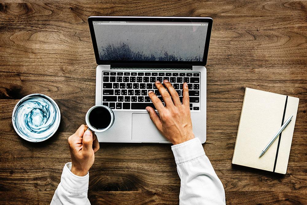 Uma foto aérea mostrando uma mesa com um notebook onde um advogado está analisando gráficos enquanto segura uma xícara de café. Os gráficos representam as possibilidades de aumentar a receita do escritório