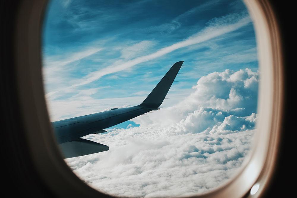 O céu visto através da janela de um avião durante o voo. Imagem representa as vantagens de um sistema de gestão digital que contenha todas as informações do escritório.