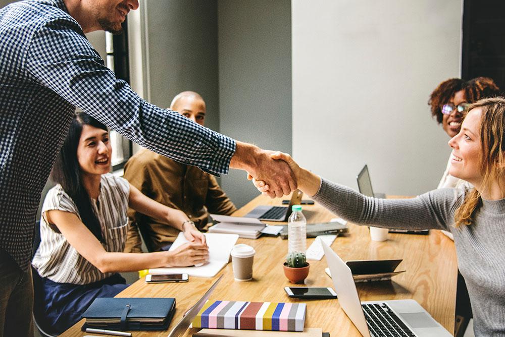 Advogados felizes em uma reunião se cumprimentando, representando as facilidades de um software de gestão