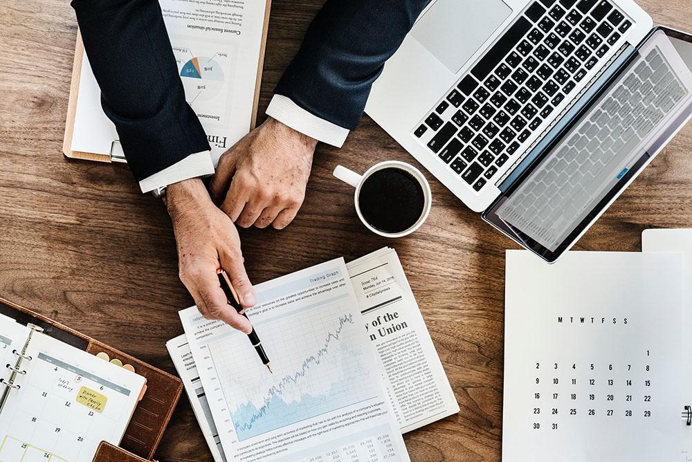 Foto aérea da mesa de um advogado onde ele aponta dados em um gráfico com uma caneta, analisando cálculos de honorários advocatícios.