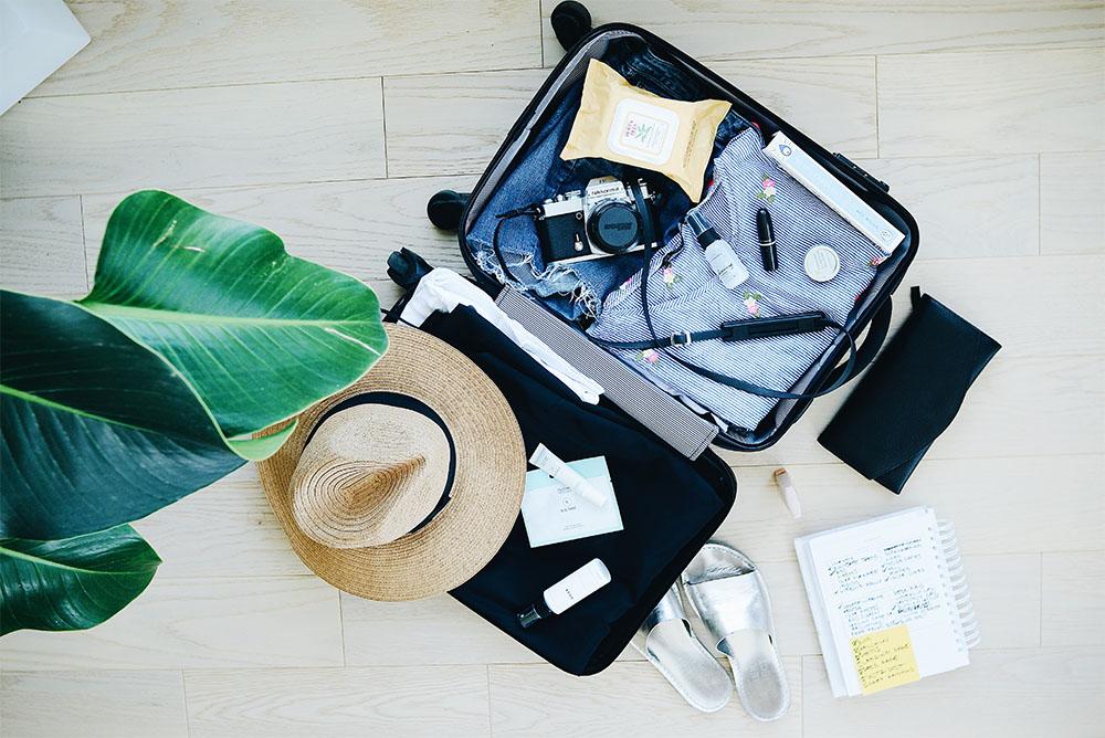 Foto aérea de uma mala sendo preenchida com diversas roupas, acessórios e utensílios, mostrando a capacidade do advogado viajar a lazer com a ajuda da gestão digital do escritório