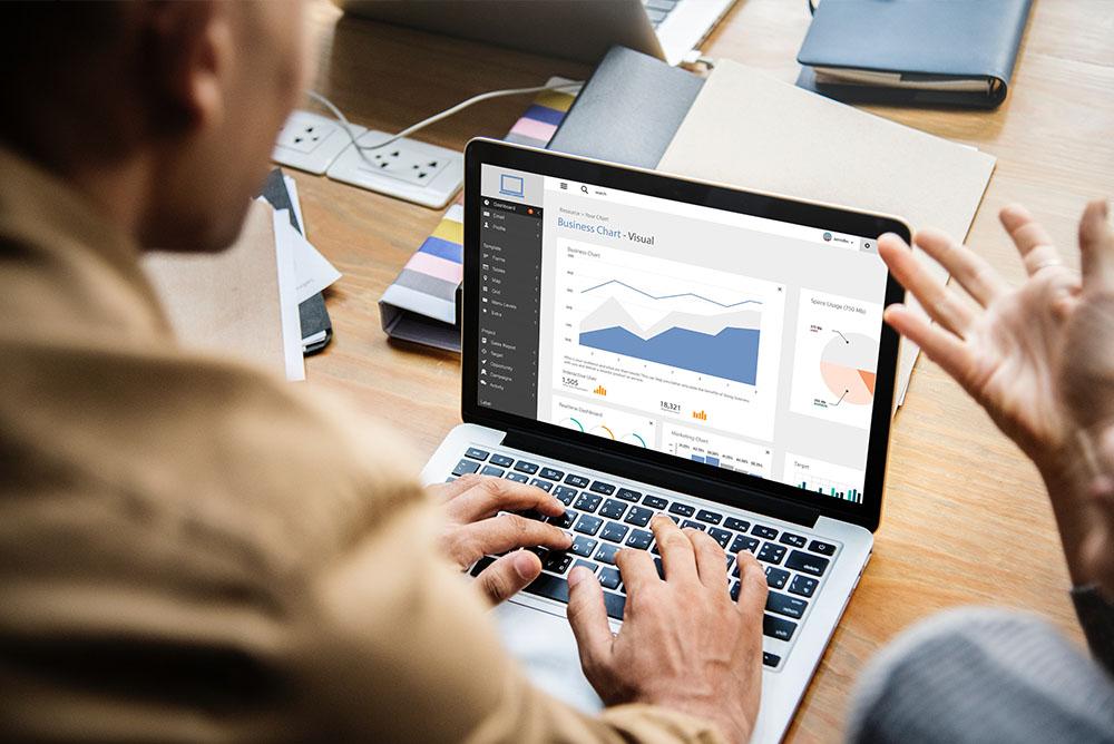 Advogado mexendo em um computador, que mostra na tela gráficos, representando o controle de produtividade do advogado