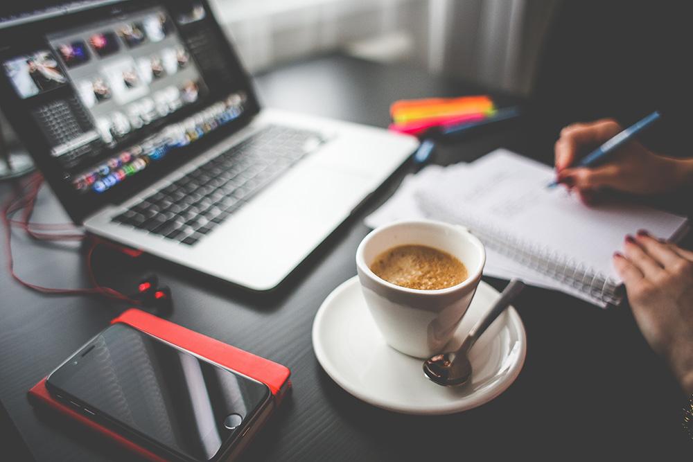 Um notebook sobre uma mesa, juntamente com uma xícara de cafée um bloco de notas onde um advogado faz algumas anotações. Representa a advocacia digital.