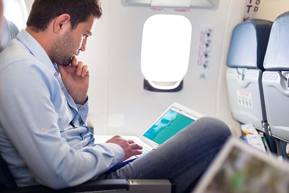 Um homem no assento de um avião com um notebook sobre o colo e administrando o escritório pela ADVBOX. Foto demonstra a possibilidade de Gerenciamento remoto na advocacia.