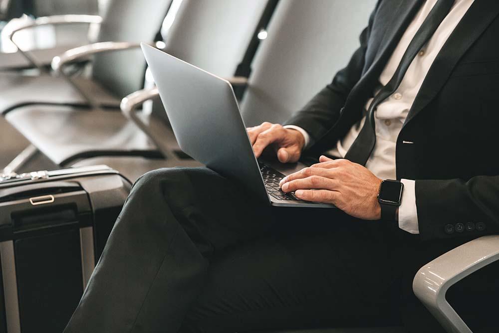Advogado de terno e gravata sentado em cadeira no aeroporto com mala ao lado e mexendo no notebook sobre o colo. Imagem representa gestão financeira em escritórios de advocacia