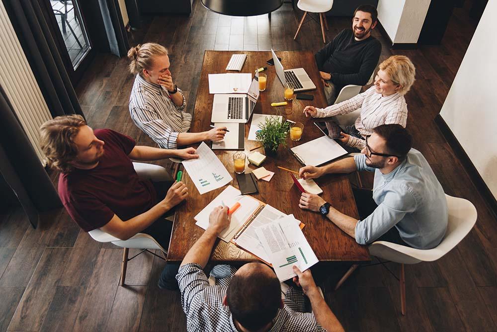 Seis pessoas (homens e mulheres) ao redor de uma mesa de madeira, análisando, gráficos, documentos, e conversando. Imagem representa a Hiperespecialização em escritórios de advocacia.