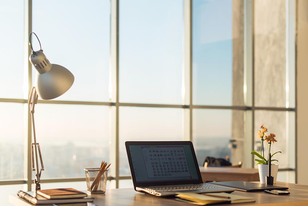 Um notebook e um abajur sobre um a mesa em frente a uma mesa com vista panorâmica. Representa a possibilidade de home office na advocacia