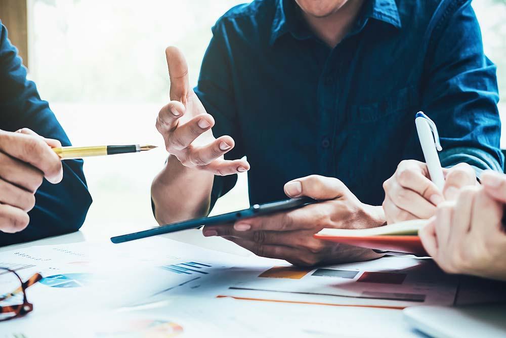 Equipe de advogados analisando anotações e dados em um tablet, representando o crescimento de escritórios de advocacia