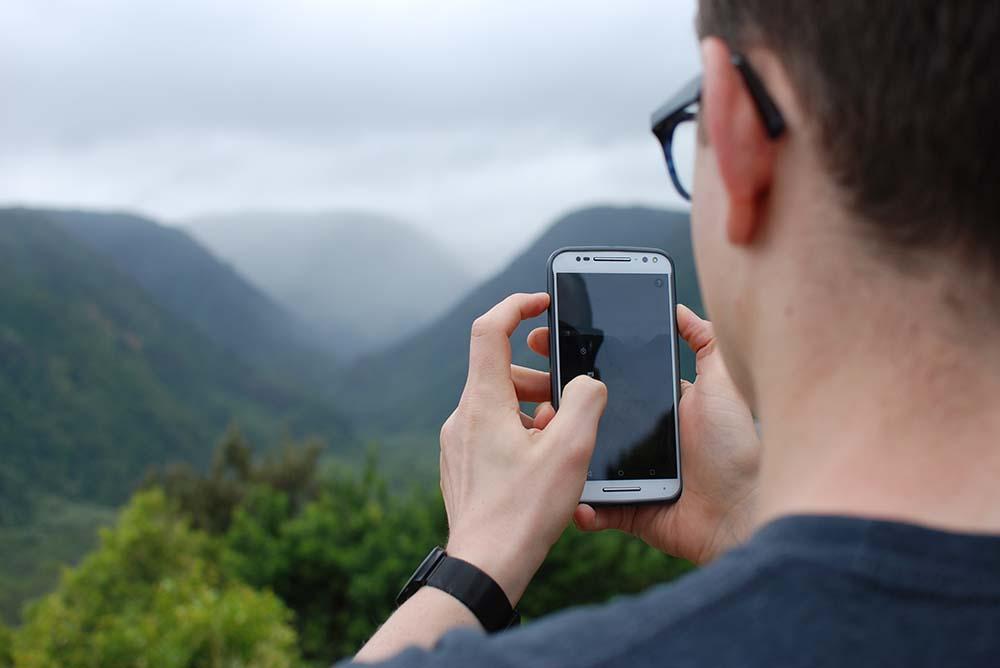 Advogado segurando celular e fotografando um vale, representando o tempo livre para advogados