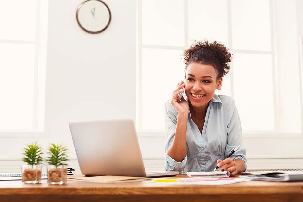 Uma advogada falando ao celular e verificando informações em um notebook enquanto sorri. Foto representa o auxílio que a advocacia digital pode trazer a quem sofre com Sobrecarga na advocacia.