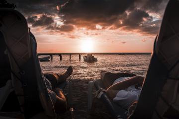 Duas pessoas deitadas em cadeiras de descanso na beira de uma praia ao pôr-do-sol. Representa a tranquilidade adquirida quando você possui um fluxo de trabalho de alta produtividade na advocacia