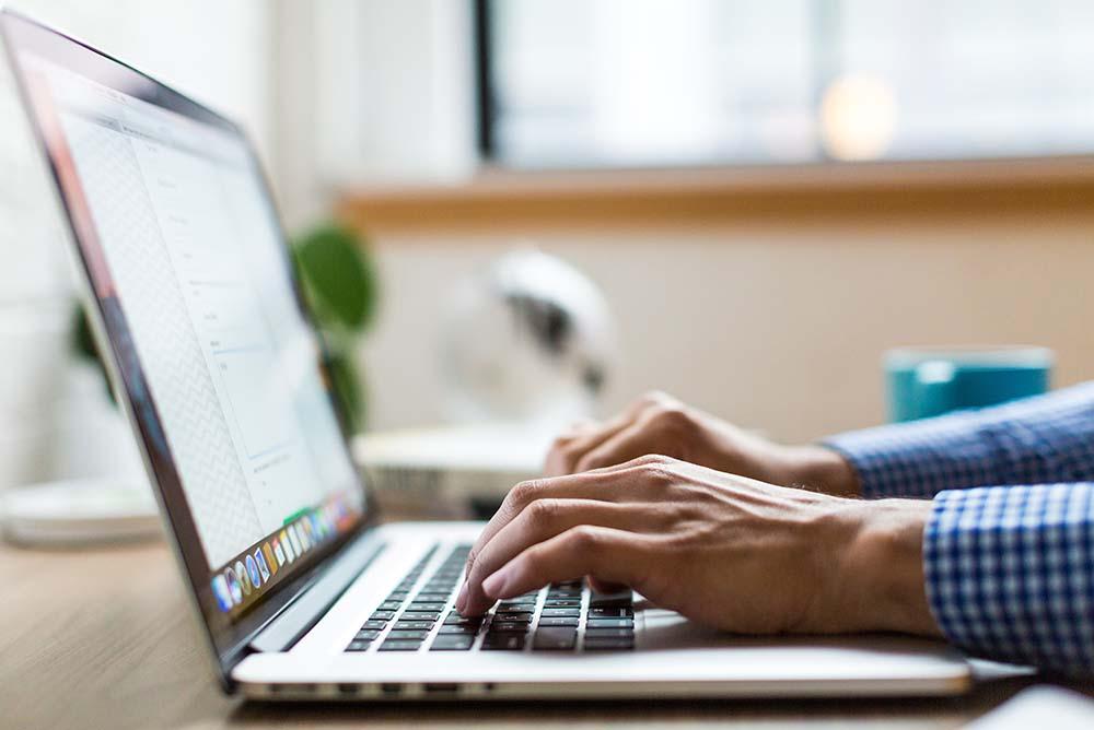 Advogado digitando em notebook, representando o engajamento digital para otimização de escritórios de advocacia