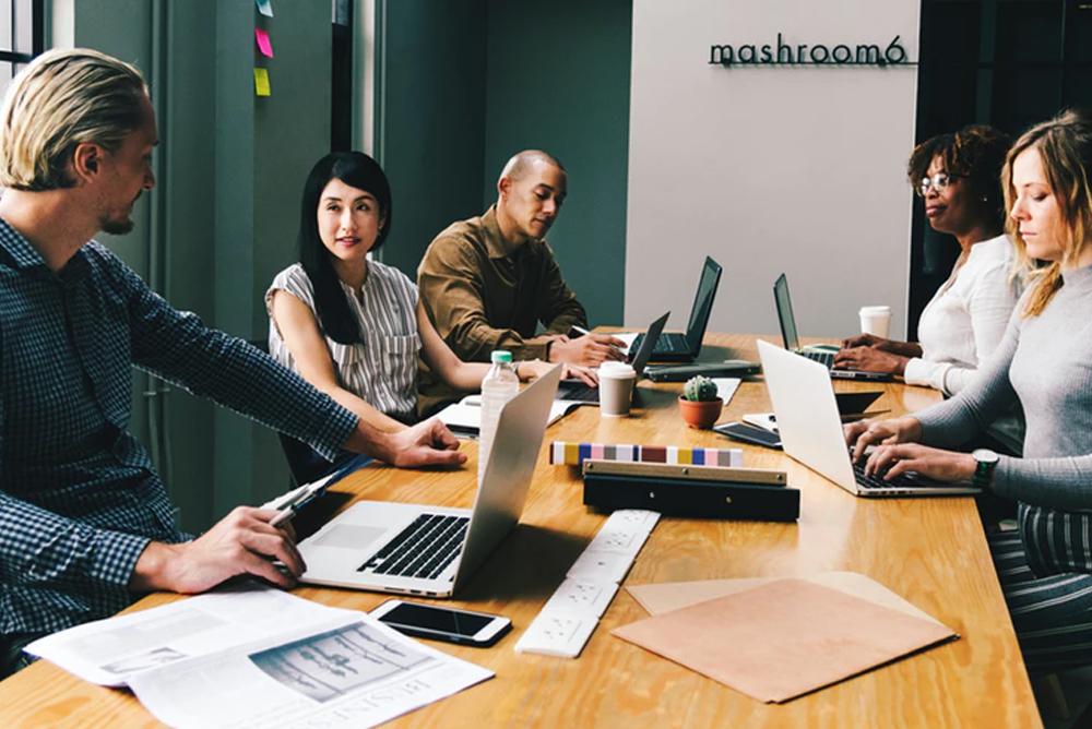 Diversas pessoas ao redor de uma mesa de reunião conversando. Representa a criação de estruturas para web service