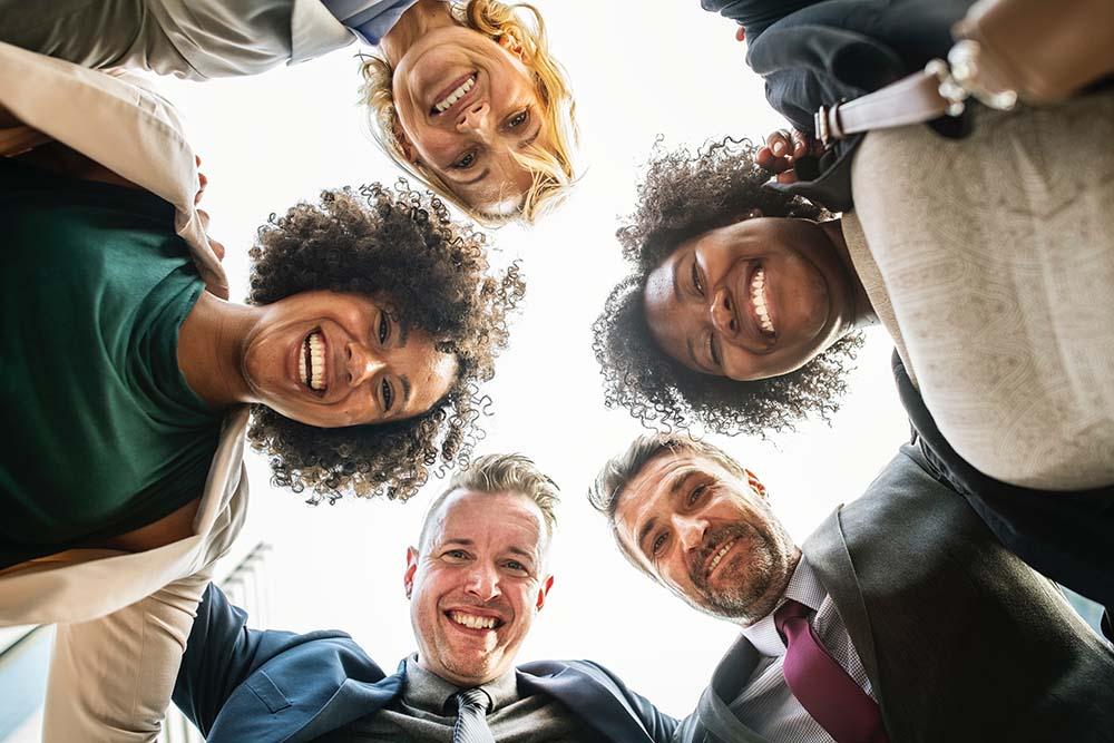 Diversos advogados e advogadas sorridentes formando um círculo. Foto representa as facuilidades ddo atendimento jurídico à distância