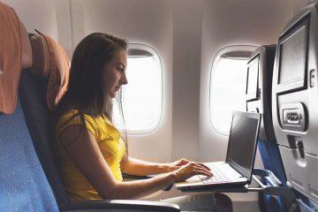 Uma mulher usando o computador para trabalhar sentada no asssento de um avião, representando o gerenciamento remoto de escritórios de advocacia