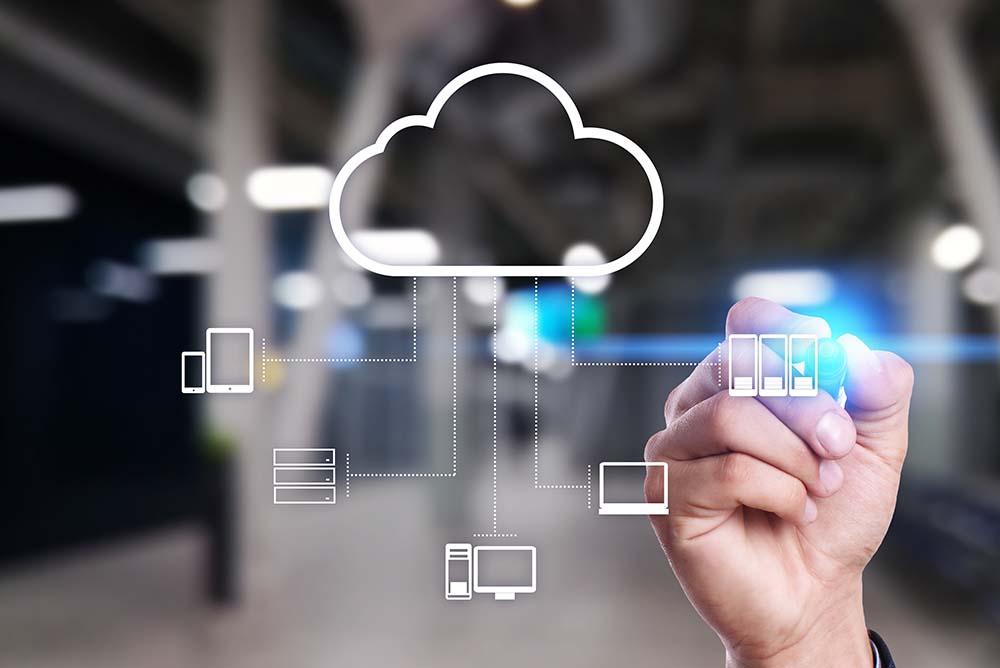 Homem desenhando em um quadro de vidro diversos elementos saindo de uma nuvem, tais como celulares, tablets, computadores e notebooks. Representa as possibilidades de atuar com um escritório virtual