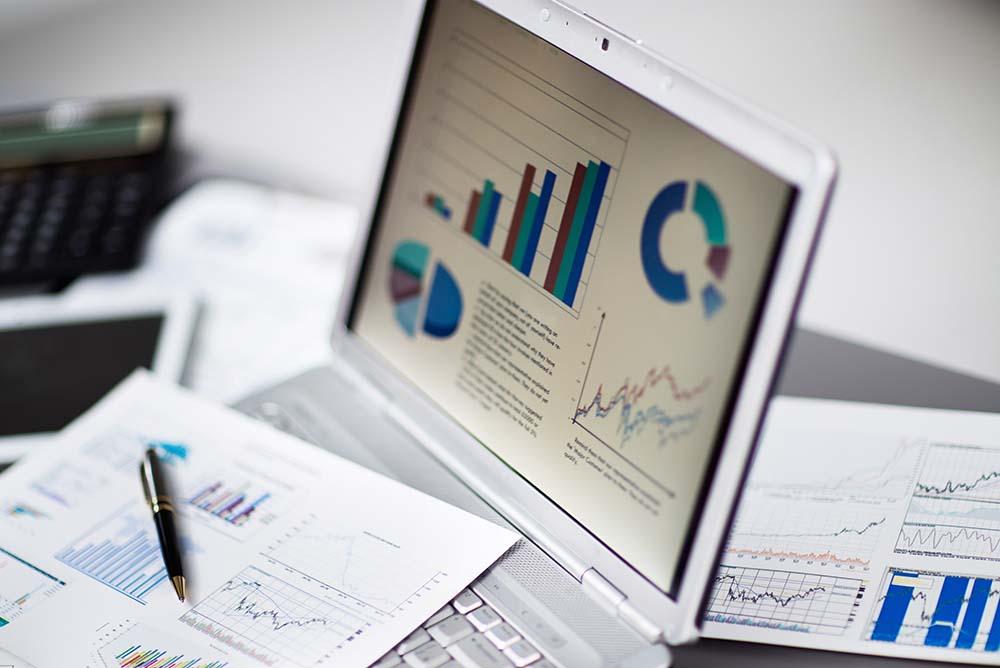 Notebook aberto, onde na tela aparecem diversos gráficos, representando os meios de medir o Crescimento do Escritório
