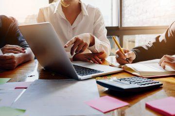 Alguns advogados em uma mesa em reunião apontando par aum notebook e com diversos documentos sobre a mesa, representando os cuidados para se ter um escritório de sucesso