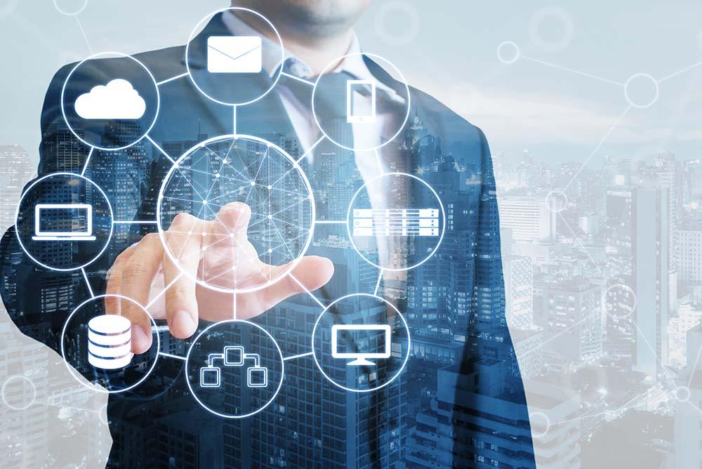 Um homem de terno tocando em uma superfício de vidro onde surgem diversos elementos relacionados à tecnologia, como engrenagens, computadores, celulares e tablets. Representa as possibilidades de ferramentas para potencializar seu escritório