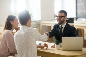 Advogado estendendo a mão apra cumprimentar clientes sorridentes, simbolizando a possibilidade de manter a clientela mesmo mudando o escritório de cidade