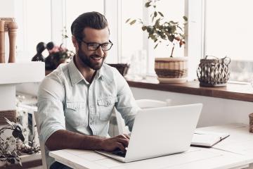 Advogado sorrindo e trabalhando em um notebook. Simboliza a melhoria de atendimento ao cliente através da ADVBOX.