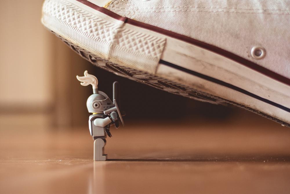 Foto mostra um brinquedo tipo lego de um personagem com armadura de guerreiro prestes a ser pisado por um pé com tênis