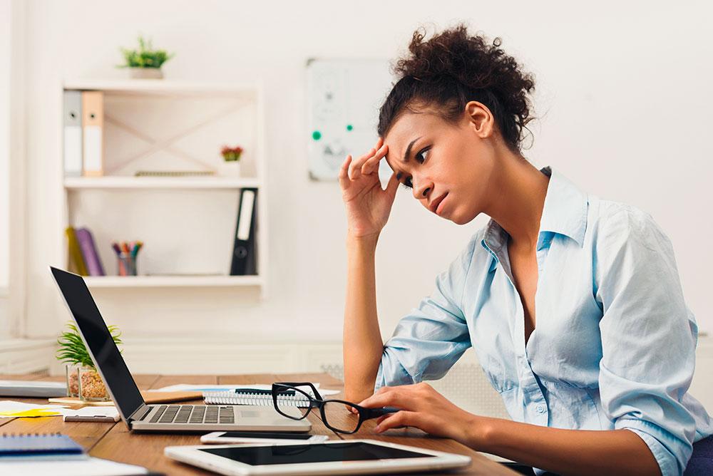 Uma advogada com semblante preocupado olhando para a tela de um notebook apoiando a testa sobre uma das mãos. Representa a dificuldade de medir a produção de um advogado