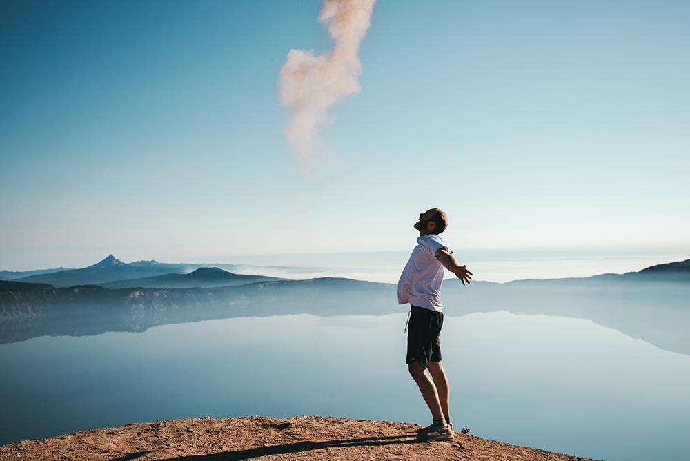Homem de braços abertos perto de um lago que reflete o céu azul.