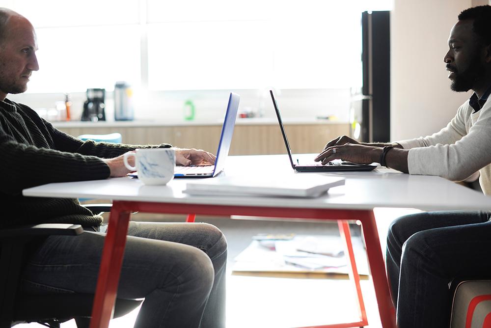 Dois homens frente à frente em uma mesa, tomando café e mexendo em notebooks. Representa a facilidade de gerenciamento de e-mail