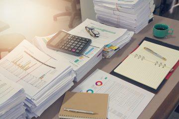 Uma mesa com diversas pilhas de relatórios e pastas, além de uma calculadora. Representa análises necessárias para identificar prejuízos no escritório
