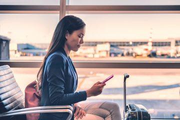 Uma advogada verificando informações em seu smartphone em um aeroporto, sentada aguardando por um voo, com sua mala repousando ao lado. Demonstra a possibilidade de manter a satisfação do cliente com atendimento à distância.
