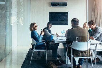 Três advogados e duas advogadas conversando e sorrindo sentados à uma mesa em um escritório bastante futuristas, com paredes de vidro. Simboliza o uso da tecnologia para qualificação da equipe.
