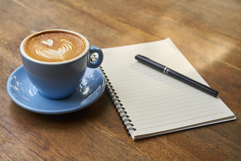 Mesa com um caderno, caneta e xícara de café ao lado.