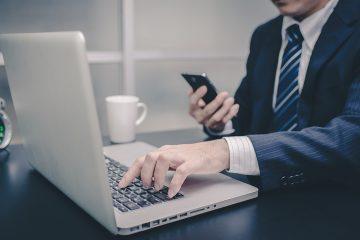 Advigado registrando origem dos clientes no notebook enquanto verifica informações no smartphone