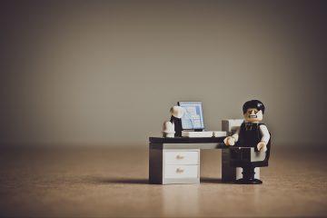 Foto de um bonequinho lego com semblante preocupado e usando roupas formais sentado em frente a uma escrivaninha com um computador.