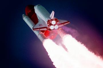 Foto de um foguete decolando com um céu azul escuro de fundo.