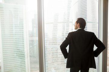 Homem de terno olhando a cidade através de uma janela de vidro com semblante pensativo.