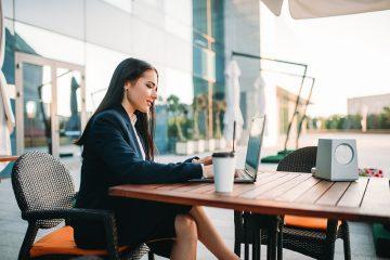 Uma advogada trabalhando em um espaço à ceu aberto em sseu notebook com o auxílio de um software jurídico
