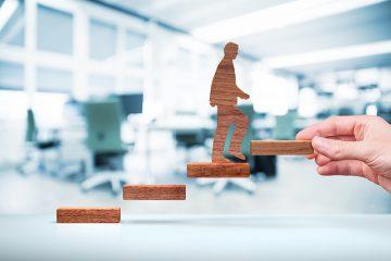 Uma mão mexe algumas peças no ar. Ela coloca um degrau em uma escada para servir de apoio a uma miniatura de advogado que está subindo. representa a possibilidade de Empreender na Advocacia