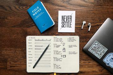 """Foto aérea de uma mesa, onde repousa um bloco de notas com diversos planos escritos. Uma caneta está sobre o caderno. Na mesa também há fones de ouvido e um adesivo escrito """"nunca se acomode"""" representa o trabalho autônomo e como medir a produtividade"""