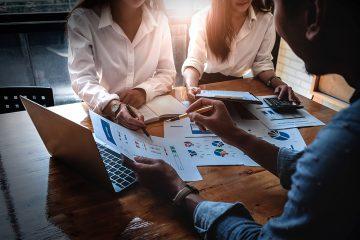 Um advogado e duas advogadas reunidos ao redor de uma mesa apontando dados em um relatório sobre controle financeiro