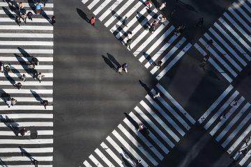 """Uma foto aérea que mostra um cruzamento de avenidas em uma cidade grande com muitas pessoas atravessando de um lado ao outro. Simboliza o tráfego de carros substituído por pessoas e reforça o paralelo que o texto faz entre """"flanelinhas jurídicos"""" e um bom atendimento na advocacia"""