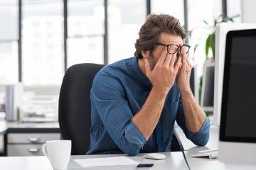 Um jovem advogado sentado em frente ao computador em seu escritório, apertando os olhos com os dedos por debaixo dos óculos, simbolizando as dificuldades do início na advocacia