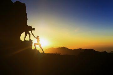 Um casal escalando uma montanha ao pôr-do-sol. O homem ajuda a mulher estendento a mão e a puxando para cima, simbolizando a escalada do sucesso na advocacia