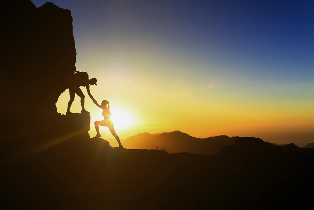 Um casal escalando uma montanha ao pôr-do-sol. O homem ajuda a mulher estendendo a mão e a puxando para cima, simbolizando a escalada do sucesso na advocacia