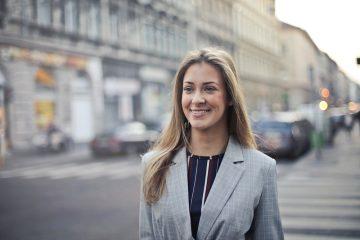 Uma advogada vestida formalmente e com elegância, caminhando sorridente pelas ruas de uma cidade bonita. Representa o advogado bem-sucedido