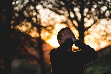 Advogado em um bosque ao pôr-do-sol com as mãos na face aparentando aflição. Representa a baixa qualidade de vida do advogado.
